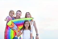 与飞行一只风筝的愉快的微笑的家庭在海滩 库存图片