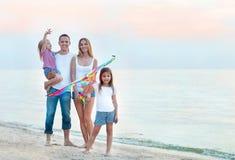 与飞行一只风筝的愉快的年轻家庭在海滩 免版税库存照片