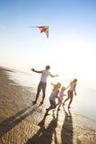 与飞行一只风筝的愉快的年轻家庭在海滩 库存照片