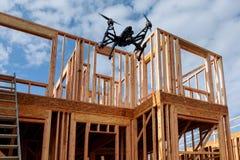与飞行在住宅建设家庭构筑的照相机的黑寄生虫quadcopter反对 免版税库存照片