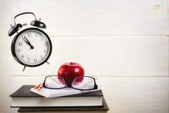 与飞行闹钟、书、笔记本和红色苹果的静物画 库存照片