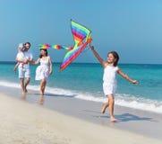 与飞行风筝的愉快的年轻家庭 免版税库存图片