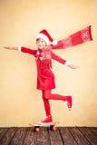 与飞行围巾的滑稽的圣诞老人孩子 免版税库存照片