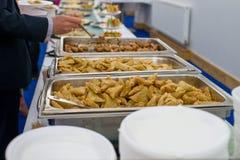 与食物宴会和胳膊的表有匙子的 免版税库存照片