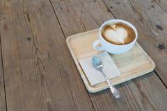 与餐巾的热的热奶咖啡在木桌上的咖啡和匙子 免版税库存图片