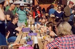 与饥饿的人民、室外饭食和的饮料的拥挤党 免版税库存照片