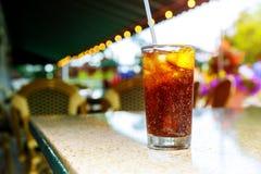 与饮料的冰冷的可乐在鸡尾酒的一个柠檬室外 免版税图库摄影