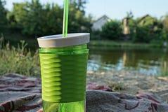 与饮料的塑料绿色玻璃和在海滩的一支管在水附近 免版税图库摄影