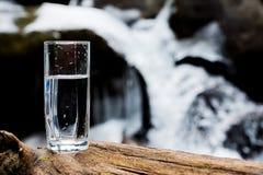 与饮用的山矿泉水的一块透明玻璃玻璃在木头站立反对迅速流程的背景 图库摄影