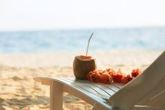 与饮用的strawand列伊的椰子在海滩长凳或轻便折叠躺椅与蓝色海洋和白色沙子开花在背景 库存照片