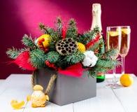 与香槟和圣诞节装饰箱子的玻璃反对桃红色 库存图片