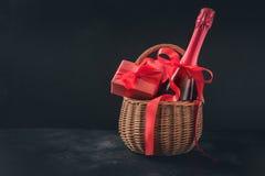 与香槟和礼物篮的情人节卡片在黑色 您的问候的空间 免版税库存图片