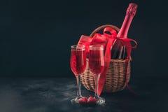 与香槟和礼物篮的情人节卡片在黑色 您的问候的空间 免版税图库摄影