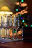 与香槟玻璃和被堆积的板材的庆祝桌在圣诞树背景 免版税库存照片