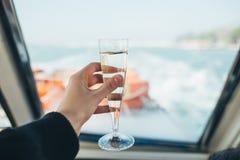 与香槟玻璃的香宾玻璃在妇女手背景中 库存图片