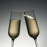 与香槟飞溅的叮当声玻璃 免版税库存图片