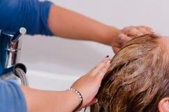 洗与香波一根长的洗染的头发,在理发交谊厅里面的手 图库摄影
