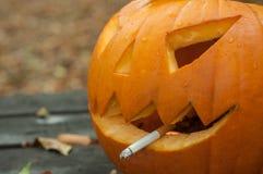 与香烟的万圣夜南瓜在秋季前面 免版税库存照片