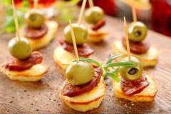与香肠加调料的口利左香肠和绿色oliv的被烘烤的土豆西班牙快餐 图库摄影