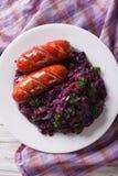 与香肠特写镜头的被炖的红叶卷心菜在板材 垂直的t 图库摄影