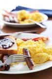与香肠连结和炒蛋的早餐。 免版税图库摄影
