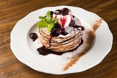 与香草冰淇淋和温暖的樱桃的巧克力薄煎饼在白色板材调味 库存图片