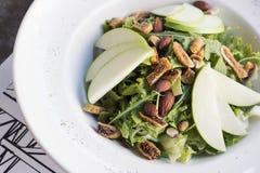 与香菜、干无花果、加香料的杏仁和苹果的健康菠菜和芝麻菜沙拉 库存图片