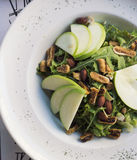 与香菜、干无花果、加香料的杏仁和苹果的健康菠菜和芝麻菜沙拉 库存照片