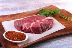 与香菜香料叶子的未加工的牛排在木切板的 为烹调准备 图库摄影