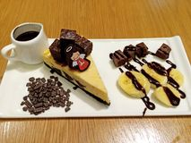 与香蕉切片和热巧克力调味汁的果仁巧克力乳酪蛋糕 图库摄影