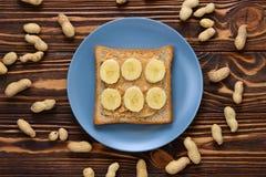 与香蕉切片的花生酱多士在木背景 免版税库存照片