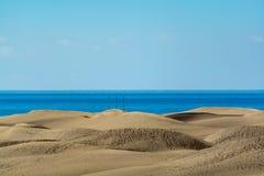 与马斯帕洛马斯和蓝色大西洋,大加那利岛,西班牙黄色含沙沙丘的风景  库存照片