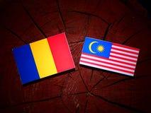 与马来西亚旗子的罗马尼亚旗子在被隔绝的树桩 向量例证