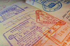 与马来西亚签证和移民控制邮票的护照页 库存图片