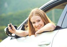 与驾驶一辆新的汽车的钥匙的妇女司机 免版税图库摄影