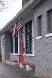 与骄傲地垂悬一面的美国国旗的咖啡馆前面 免版税库存图片