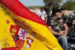 与骑自行车的人的西班牙旗子背景肉猪集会的 库存照片