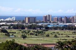 与高尔夫球场和海洋的城市地平线 免版税库存图片