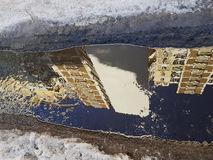 与高层建筑物、高淡黄色墙壁、深蓝天空、肮脏的沥青和灰色雪的镜象的一个横向水坑 免版税库存照片