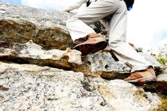 与高涨的英尺启动攀登岩石墙壁 库存照片