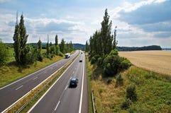 与高速公路主导的白杨树胡同、高速公路乘驾三汽车和卡车的农村风景 免版税库存图片