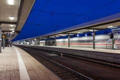 与高速旅客列车的现代火车站在行动的铁轨 铁路平台在晚上在纽伦堡 免版税库存照片