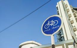 与高都市大厦的圆自行车赛车道标志板在背景中 库存照片