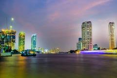 与高buidings的夜间地平线查奥Praya河在曼谷,泰国 库存照片