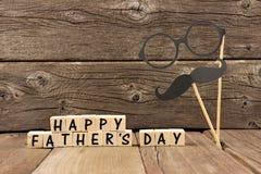 与髭和玻璃的愉快的父亲节块反对木头 库存照片