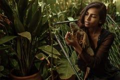 与鬣鳞蜥的美丽的女性画象和树 免版税库存图片