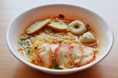与鱼丸和红色烤肉猪肉的稀薄的面条在辣汤 库存图片