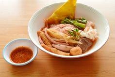 与鱼排行和虾球的米细面条在红色汤 库存图片