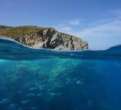 与鱼浅滩的地中海岩石海岸  免版税库存照片