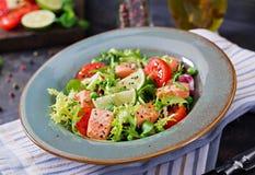 与鱼的健康沙拉 被烘烤的三文鱼、蕃茄、石灰和莴苣 免版税库存图片